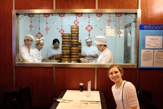 Christina poses in the foreground with the steamed bun cooks doing their thing in the background.